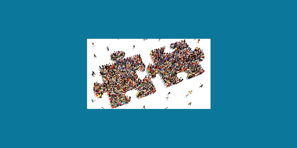 Image taken from an aerial view of people standing in groups, making the shape of two jigsaw pieces coming together.